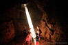 Kids playing with the beam of light inside a Lava Tube