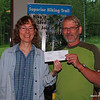 Why is this woman smiling (Gayle Coyer)?  That is because Rudi Hargescheimer of the Midwest Mountaineering has presented SHTA with a $5,000 check from Midwest Mountaineering.  Congratulations Superior Hiking Trail Association!