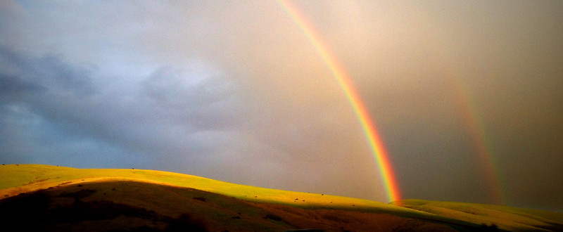 A rare double rainbow appears over the rolling hills of San Luis Obispo County, California after a quick-moving storm brought much needed rain to the area recently.  ©2014 Eric Parsons Photography