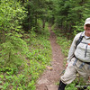 Why is this man smiling?   It is because he is hiking on cleared trail.  Note that the black spruce and balsam fir on the left have been left standing and not cut.   In a few years  they will create a canopy that will block light and slow down brush growth.