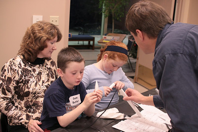 Mark Joseph helps a couple of students with their shock cord installations.  Photo by Greg Smith