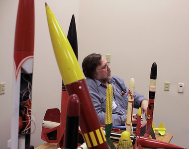 Christopher Deem with some of the rockets used in the introductory presentation and slide show.  Photo by Greg Smith
