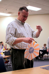 Robert Brunner demonstrates how to form the loops to tie the parachute to the rocket.  Photo by Greg Smith
