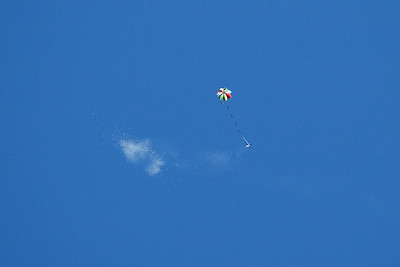 The rocket deploys a colorful parachute (and a large cloud of recovery wadding) prior to making a safe descent and landing.  Photo by Alan Carroll