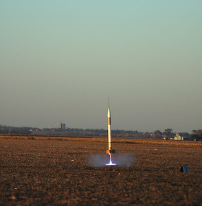 Ignition of Jonathan Sivier's LOC EZ-I65 just as the sun was setting at the end of the launch.  Note the Blue Thunder flame illuminating the launcher's blast deflector.  Photo by Alan Carroll