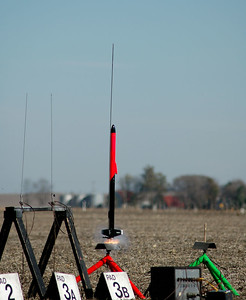 Greg Smith's Helios-2, a smaller all-fiberglass rocket with an onboard video camera and transmitter, caught almost at the moment of ignition with an Aerotech H128-M motor.  Photo by Alan Carroll