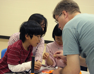 Jonathan helps some students tie the shock cord and parachute to the nose cone.  Photo by Greg Smith