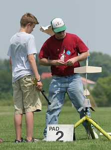 Jonathan helps an IAI camper hook up his boost glider on the pad.  Photo by Greg Smith