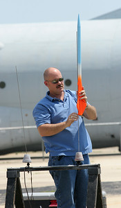 Tim Dixon loads one of his own rockets, with a D12 motor, to demonstrate to the group.  Photo by Greg Smith
