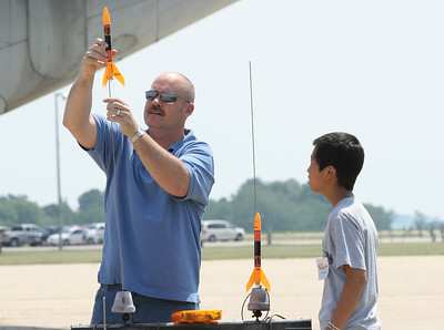 Tim Dixon assists a camper in loading his rocket on the pad.  Photo by Greg Smith