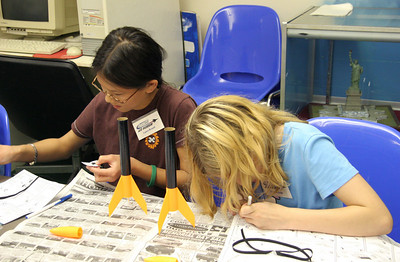Laura Brandt and Skye Little work on the shock cord mounts for their rockets.  Photo by Greg Smith