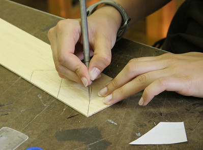 A student carefully cuts out the balsa fins for the rocket she designed.  Photo by Greg Smith
