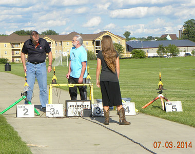 Dan West (center) helping two of the Rotary Club members load the rockets on the pads. photo by Christopher Brian Deem