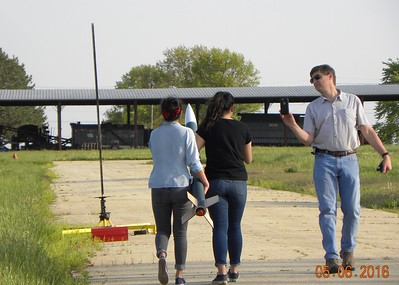 Two of the students take the rocketto the pad, while Mark captures it on video.
