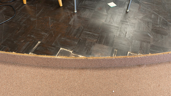 Before - Closeup of damaged stage flooring.