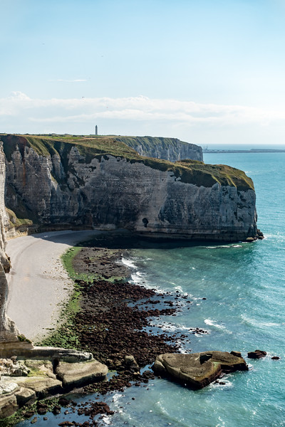 Cliffs in the foreground (Pointe de la Courtine - the point of the curtain) with the Antifer lighthouse (phare d'Antifer) on the horizon.