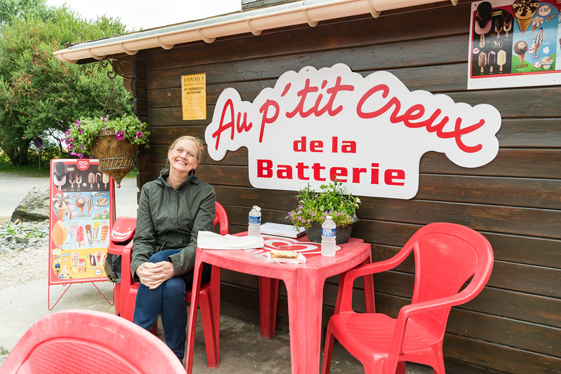 """The very red chairs and table at """"Au p'tit creux de la Batterie"""" at Longues-sur-Mer Batterie, a German gun battery. Bryan had another croque monsieur and Naomi had a ham and cheese panini. Bryan discovered the Miko ice cream bars (double caramel in this case) were quite good."""