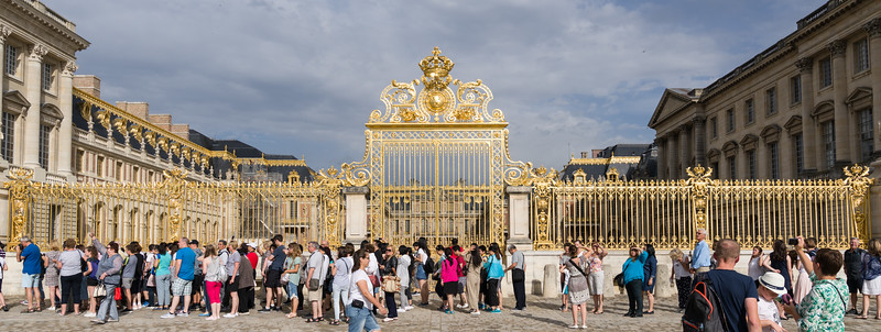 The main gates lit up by the sun, and with many people around.