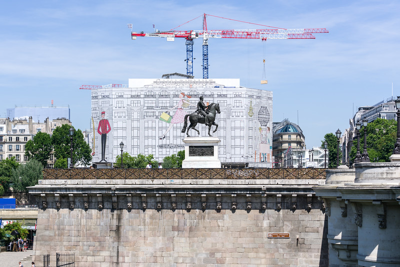 Statue of Henry IV on horseback (Statue équestre d'Henri IV) with all the love locks in front and a mondern build going up behind. (All the love locks were removed from le Pont des Arts a few years ago.)