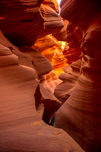 A person in the bottom of the slot canyon for perspective.
