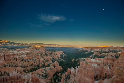 With just a splash of the setting sun hitting the Bryce Canyon Amphitheater, the moon is bright in the darkening sky.