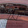 Red Oxidized Junkyard sedan rear window into steering wheel