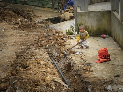 A young construction worker on a walk through a small village