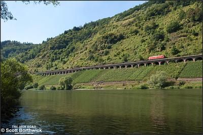 185 038 hauls an train of empty steel flats along the 786m long Hangviadukt (slope viaduct) at Pünderich on 27/08/2016.