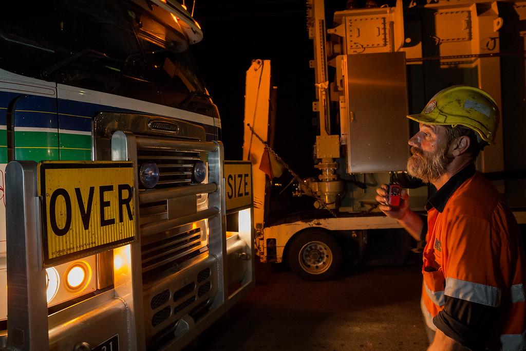 Men offloading cargo from large trucks