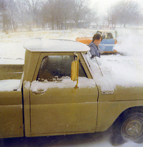 Dad scraping snow of truck on Land 1975