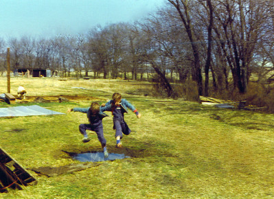 Bobbie & Brian jumping over puddle on Land 1975