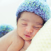 Baby boy sleeping in newborn pose with blue nappy and knitted hat