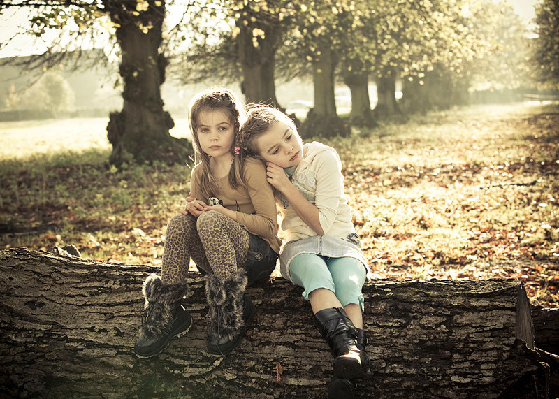 Two girls sitting on log
