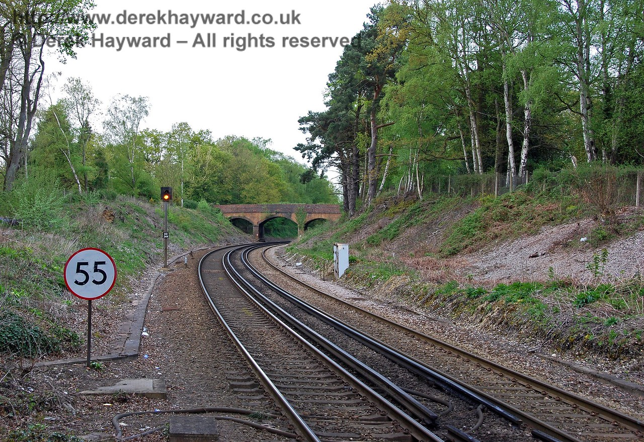 Turning round, this is the view north from Dormans Station. On the left a headshunt used to run beyond the speed limit sign.  On the right a siding ran towards the bridge past the gray apparatus case. At the end of the northbound platform a signal box stood on the left. 03.05.2008