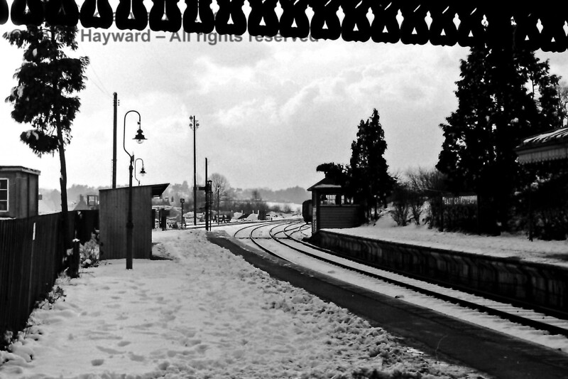 "Brrrrr!  Looking south from East Grinstead on a snowy Valentine's Day in 1970.  The siding behind the signal box (""Up Siding No.2"") can be seen occupied by coaching stock.  This siding terminated just before the viaduct at the buffer stop pictured in another  photograph. Eric Kemp retains all rights to this image."