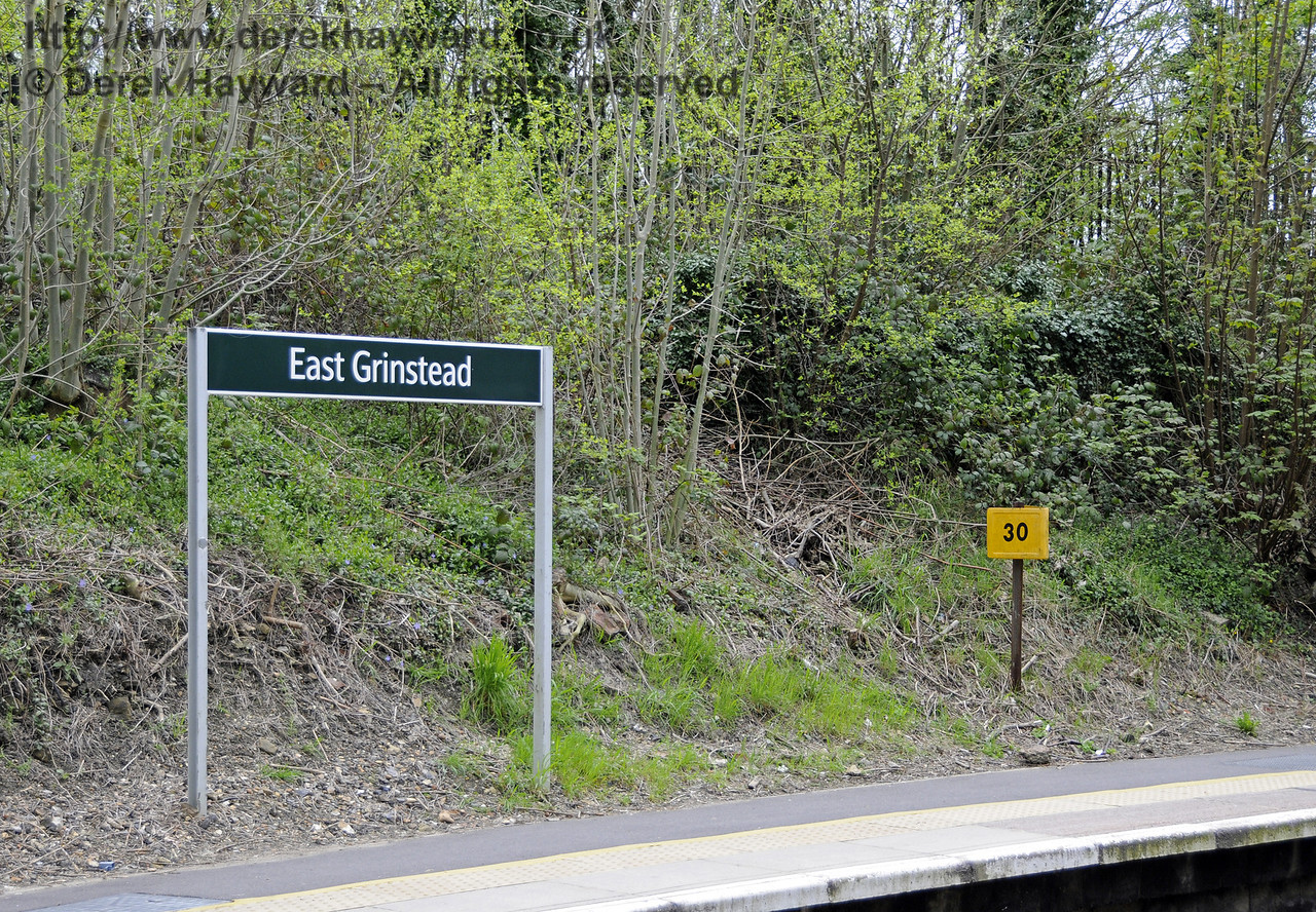 A station name in Southern colours, together with a Network Rail milepost.  The mileage is different to that shown on Bluebell mileposts, which indicate the distance from Culver Junction.  East Grinstead Station, Network Rail.  05.04.2014  10161