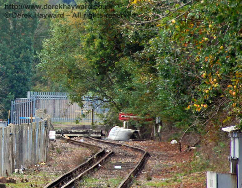 In 2008, at the limit of the long lens then available, this view shows the original Network Rail buffer stop, with the track curved towards the viaduct (sidings originally crossed the viaduct). Beyond is the grey security gate at the northern end of the viaduct, and the parapet can just be seen through the fence.  Note the gap in the conductor rail just before the track curves, and the temporary buffer at the end of the line. 18.10.2008.  0133/E2