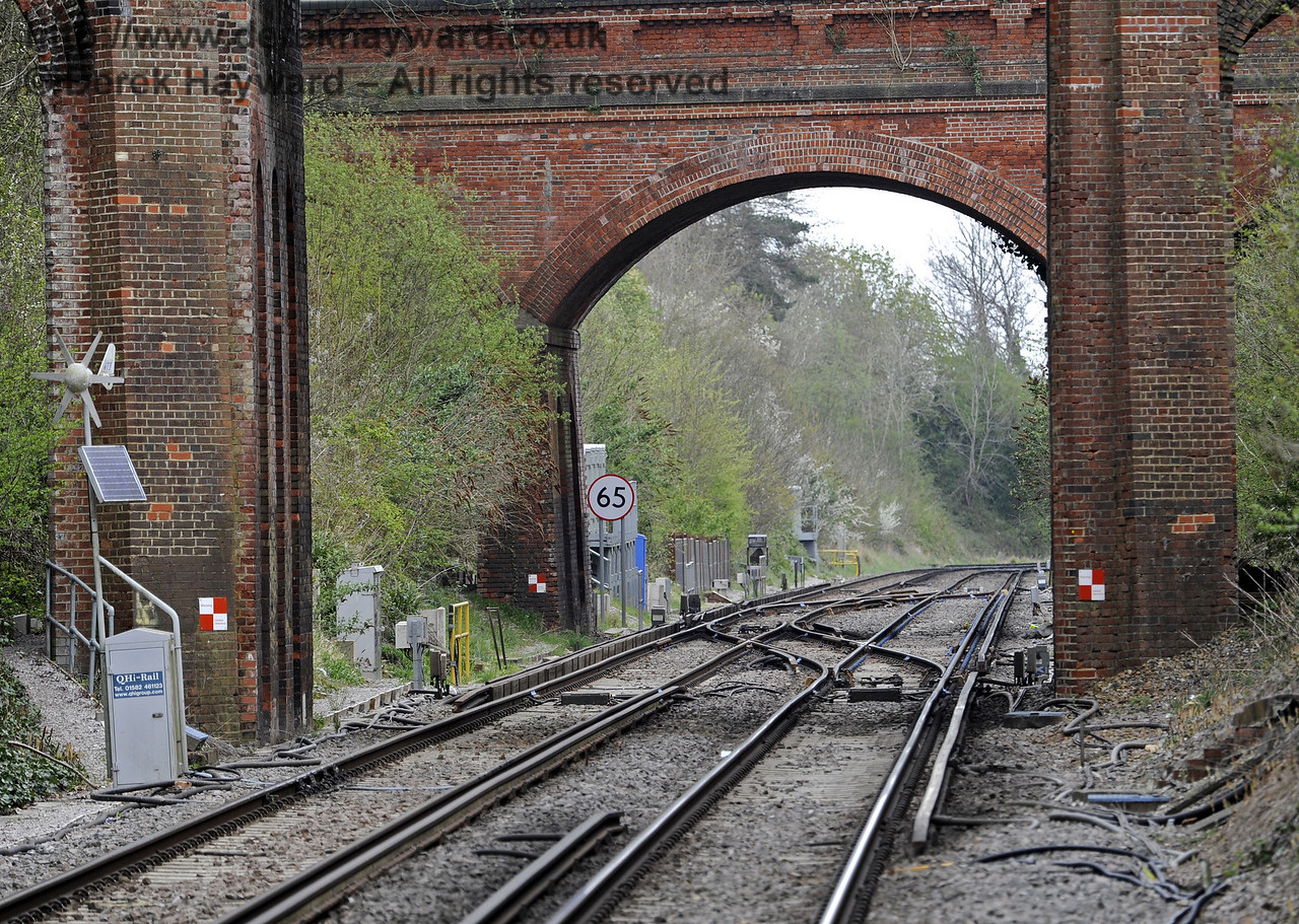 Looking north from Platform 2 with a longer lens.  The apparatus case on the left marked QHi-Rail is a solar and wind powered rail lubricator.  The lubrication points can be seen attached to the track adjacent to the case.  East Grinstead Station, Network Rail.  05.04.2014  8832