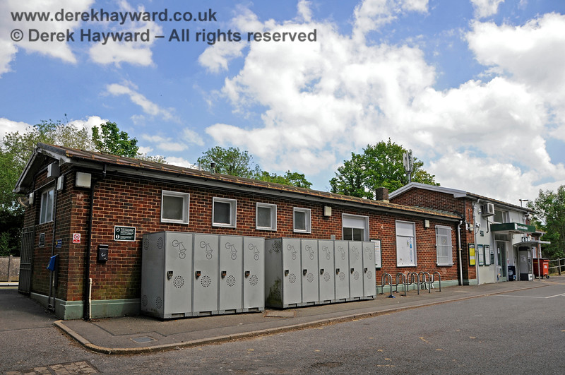 """Hurst Green Station building looking south.  The grey cabinets are cycle lockers, which is a good idea for security, but they don't enhance what is already a very drab station building.  On the extreme left is the """"out of hours"""" entrance for when the building is locked, but it's presence at the far end of the forecourt is not very obvious to strangers.  31.05.2021 20910"""