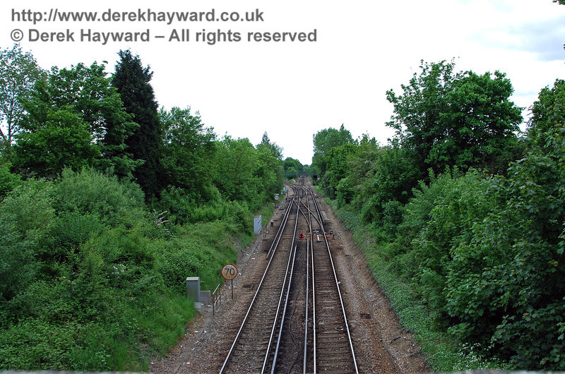 Looking south from the road bridge, with the site of the former Hurst Green Halt directly below and the junction beyond.  Points provide a facility for trains to reverse here. When the Halt was open two unusually tall southbound starting semaphore signals for the junction stood about where the 70mph speed restriction sign is located. They were more than double the height of the two storey signal box that was located at the junction, and required because of the difficult sighting caused by the road bridge to the north. 18.05.2008