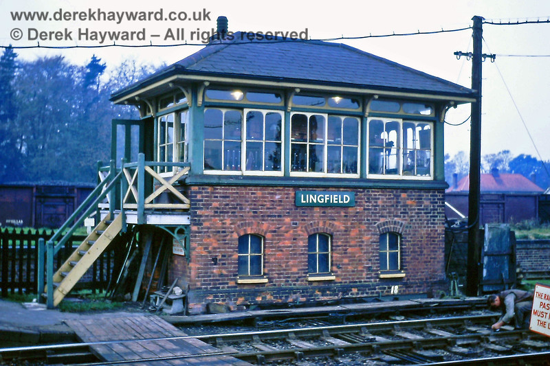 Lingfield Signal Box pictured on Sunday 10 November 1968.  The box stood at the northern end of the northbound platform.  The goods dock with grassed top can be seen behind the box.  Someone is on the track to the right; high visibility clothing did not feature heavily in those years.  Eric Kemp retains all rights to this image.