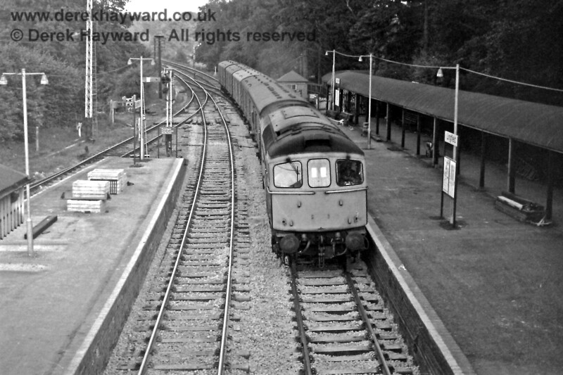 The covered way to the race course is on the right as D6571 passes through on 14 July with the 20:35 from East Grinstead.  The train consists of parcels vans carrying flower traffic.  Eric Kemp retains all rights to this image.