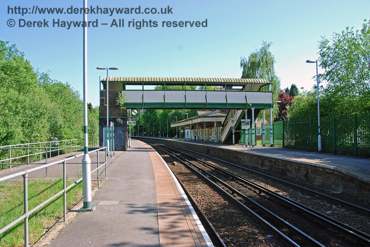 Another view taken in 2008 looking south under the footbridge from the northern end of Lingfield Station. A bay platform was formerly behind the fence on the right, and two tracks ran alongside the left hand side of the southbound platform, one of which was a siding. The fence on the left now blocks the disused platform edge. 11.05.2008