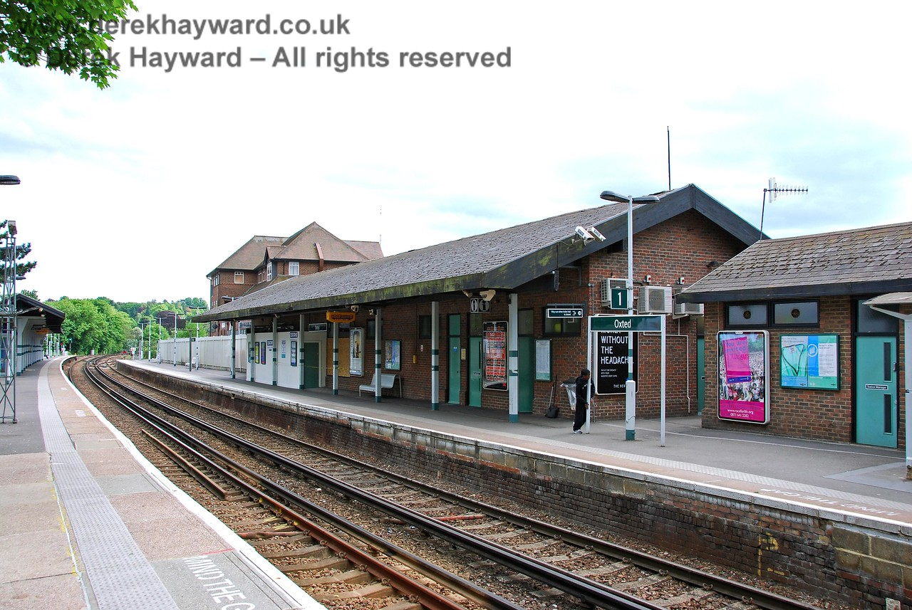 The original station and canopies at Oxted have long been demolished, and have been replaced by a more modern building of brick construction.  Refurbishment was in progress at the time this picture was taken and a hoarding can be seen at the end of the building. Additional shelter is given by the canopy on the northbound platform. 18.05.2008