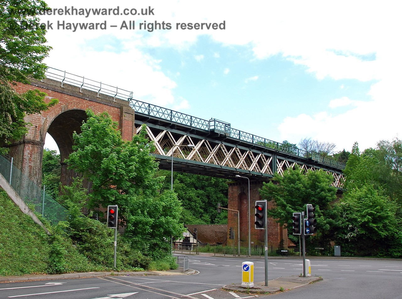 Oxted Viaduct has a short section of brick arches on the northern side, but consists mainly of a lattice box girder design which was favoured by the line's engineer, James Firbank.  This design can be seen on all major bridges from Croydon to East Grinstead.  This view, which is slightly obstructed by trees, looks south from the western side. 18.05.2008