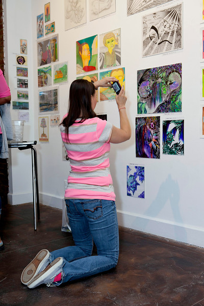 Former inmate (and artist!) Jennifer Brown photographs another artist's work at the reception.