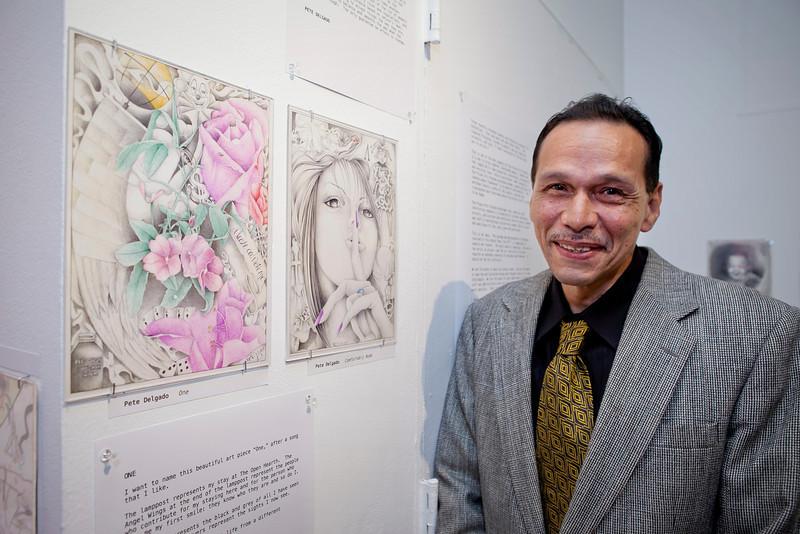 Artist Pete Delgado with his artwork.