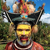 Huli Tribe warrior in his village. The Huli are not a peaceful tribe.  They fight primarily for three reasons: land, pigs and women, and in that order