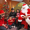 """Santa"" (aka: Tom Stupakewicz), hands out gifts to kids L-R, Ava Bettencourt 12, Ari Martinez 17 months, Calvin Bettencourt 13, Alana Bettencourt 7. SUN/David H. Brow"