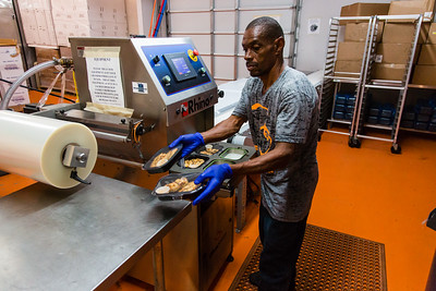 George Tripp removes freshly sealed food trays from the automatic package sealing machine at Fuel Foods on Thursday, November 5, 2015. (Joseph Forzano / The Palm Beach Post)